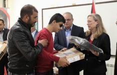 17 year old student Ahmed* receives his new laptop from the Palestinian Minister of Social Development and oPt Country Director
