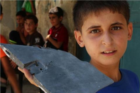 Salem *, 14 years old, holding shrapnel that destroyed his home in Gaza City. *name has been changed to protect his identity.